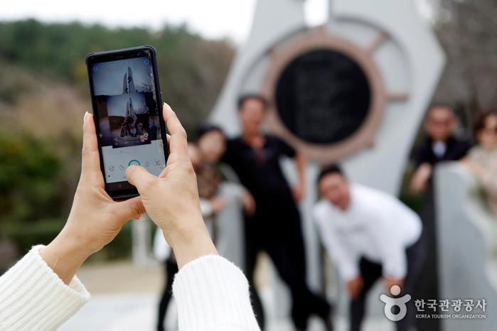 노래비 앞에서 기념사진을 찍는 사람들