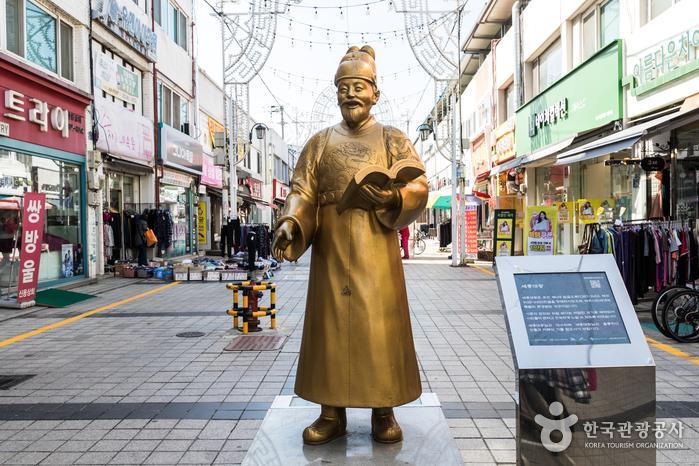 인자한 표정으로 책을 들고 있는 세종대왕 동상